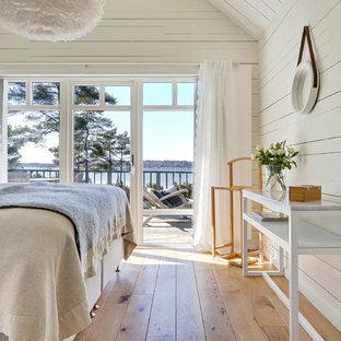 Foto på ett mellanstort maritimt sovrum, med vita väggar och brunt golv