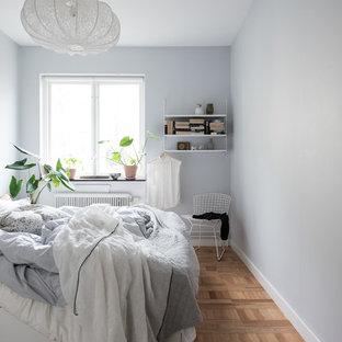 Nordisk inredning av ett huvudsovrum, med mellanmörkt trägolv, beiget golv och grå väggar