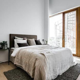Inredning av ett skandinaviskt mellanstort sovrum, med vita väggar, ljust trägolv och beiget golv
