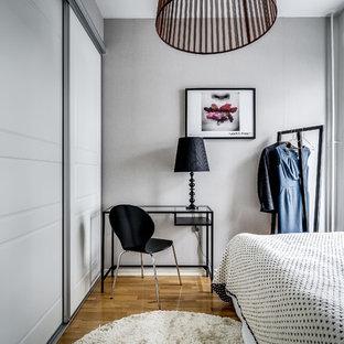 Inspiration för ett nordiskt sovrum, med vita väggar, mörkt trägolv och brunt golv