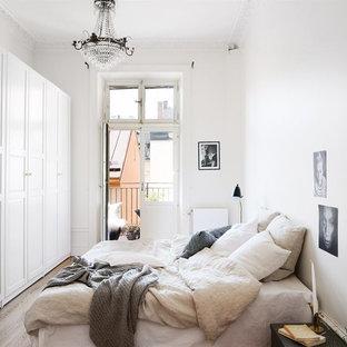 Inredning av ett klassiskt stort sovrum, med vita väggar och mellanmörkt trägolv