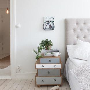 Diseño de habitación de invitados nórdica, grande, sin chimenea, con paredes blancas y suelo de madera clara