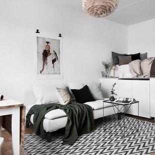 Foto på ett minimalistiskt sovrum, med vita väggar, ljust trägolv och beiget golv