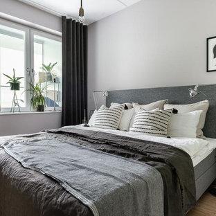 Inspiration för minimalistiska huvudsovrum, med grå väggar och ljust trägolv