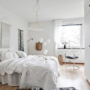 Idéer för ett skandinaviskt sovrum, med vita väggar, mellanmörkt trägolv och beiget golv