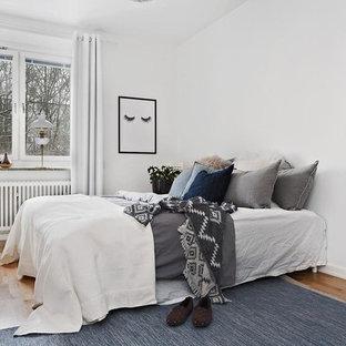 Bild på ett mellanstort skandinaviskt huvudsovrum, med vita väggar, mellanmörkt trägolv och beiget golv