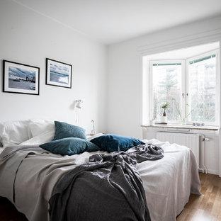 Bild på ett skandinaviskt sovrum, med vita väggar och ljust trägolv