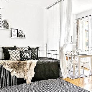 Nordisk inredning av ett litet sovrum, med vita väggar, mellanmörkt trägolv och beiget golv