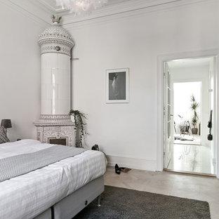 Diseño de dormitorio principal, nórdico, de tamaño medio, con suelo de madera clara, suelo beige, paredes blancas, estufa de leña y marco de chimenea de metal