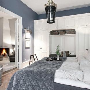 Inspiration för mellanstora minimalistiska huvudsovrum, med blå väggar, beiget golv och ljust trägolv