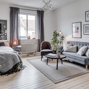 Inspiration for a mid-sized scandinavian master light wood floor bedroom remodel in Gothenburg with white walls
