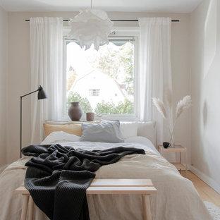 Inredning av ett skandinaviskt sovrum, med beige väggar, ljust trägolv och beiget golv