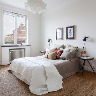 Imagen de dormitorio principal, escandinavo, de tamaño medio, sin chimenea, con paredes blancas y suelo de madera clara