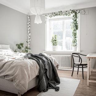 Idéer för mellanstora minimalistiska huvudsovrum, med grå väggar, mellanmörkt trägolv och brunt golv