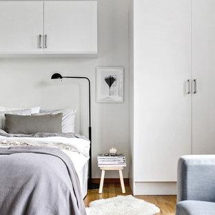 Esempio di una camera matrimoniale nordica con pareti bianche, pavimento in legno massello medio e pavimento arancione