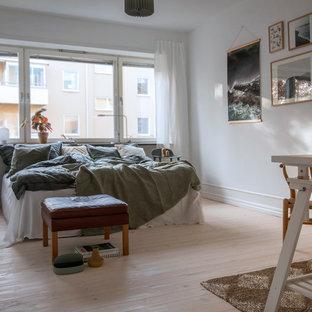 Idéer för att renovera ett nordiskt huvudsovrum, med vita väggar, ljust trägolv och beiget golv