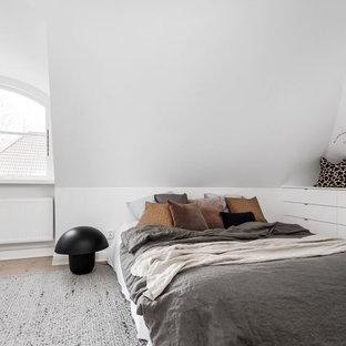 Exempel på ett litet nordiskt sovrum, med vita väggar, ljust trägolv och brunt golv