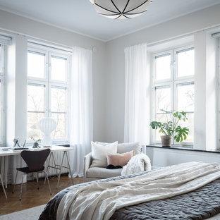 Foto på ett minimalistiskt sovrum, med grå väggar, mellanmörkt trägolv och brunt golv