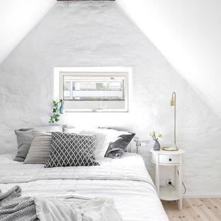 Foto på ett litet lantligt sovloft, med vita väggar och ljust trägolv