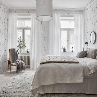 Exempel på ett stort skandinaviskt huvudsovrum, med grå väggar, ljust trägolv och grått golv