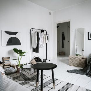 Scandinavian bedroom in Gothenburg with white walls, painted wood flooring and white floors.