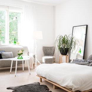Nordisk inredning av ett sovrum, med vita väggar, ljust trägolv och beiget golv