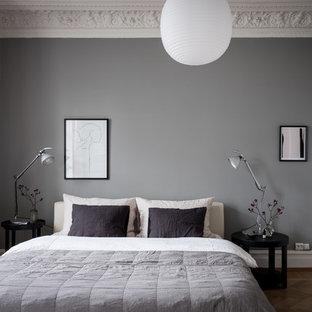 Inredning av ett minimalistiskt sovrum, med grå väggar, mellanmörkt trägolv och brunt golv