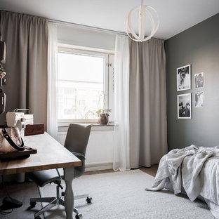 Inredning av ett nordiskt sovrum, med grå väggar, mellanmörkt trägolv och brunt golv