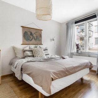 Idéer för att renovera ett minimalistiskt sovrum, med grå väggar, mellanmörkt trägolv och brunt golv