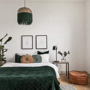 Idéer för att renovera ett nordiskt gästrum, med vita väggar, mellanmörkt trägolv och brunt golv