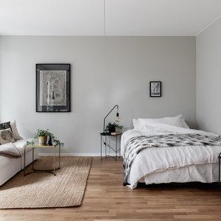 Idéer för mellanstora skandinaviska sovrum, med grå väggar, mellanmörkt trägolv och brunt golv