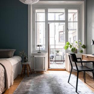 Idéer för ett minimalistiskt sovrum, med blå väggar, mellanmörkt trägolv och brunt golv