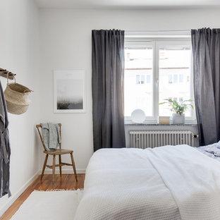 Idéer för att renovera ett minimalistiskt gästrum, med vita väggar, mellanmörkt trägolv och brunt golv