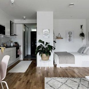 Idéer för små minimalistiska sovrum, med vita väggar, mellanmörkt trägolv och brunt golv
