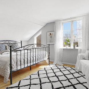 Bild på ett mellanstort nordiskt sovrum, med grå väggar och ljust trägolv