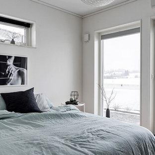 Bild på ett nordiskt huvudsovrum, med grå väggar, ljust trägolv och beiget golv