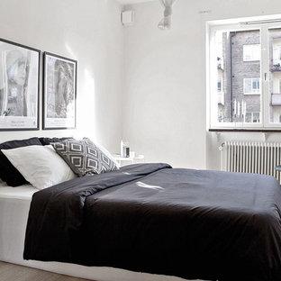 Inredning av ett minimalistiskt sovrum, med vita väggar och ljust trägolv