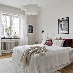 Idéer för ett mellanstort minimalistiskt sovrum, med vita väggar, mellanmörkt trägolv och beiget golv