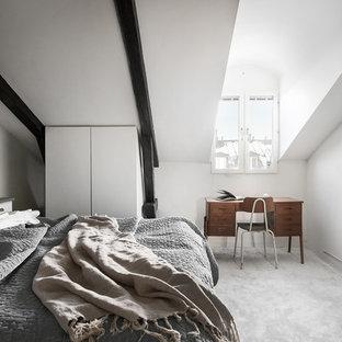 Nordisk inredning av ett huvudsovrum, med vita väggar, heltäckningsmatta och grått golv