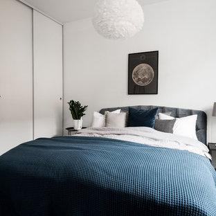 Foto på ett skandinaviskt gästrum, med vita väggar, mörkt trägolv och brunt golv