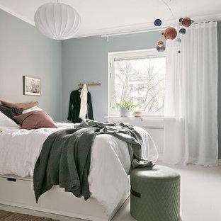 Inredning av ett minimalistiskt sovrum, med blå väggar, målat trägolv och vitt golv