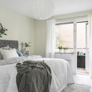 Bild på ett nordiskt sovrum, med vitt golv, gröna väggar och målat trägolv