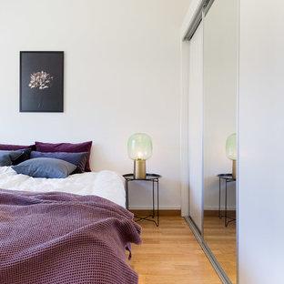 Foto de dormitorio principal, escandinavo, de tamaño medio, con paredes blancas y suelo de madera en tonos medios