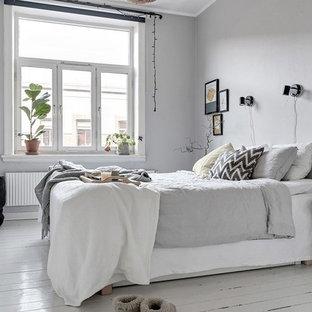 Inredning av ett minimalistiskt sovrum, med grå väggar, målat trägolv och vitt golv