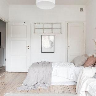 Idéer för ett mellanstort nordiskt sovrum, med vita väggar, ljust trägolv och beiget golv