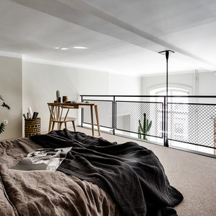 This is an example of a mid-sized scandinavian loft-style bedroom in Stockholm with carpet and white walls.