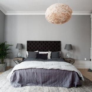 Foto på ett mellanstort minimalistiskt huvudsovrum, med grå väggar, ljust trägolv, en öppen vedspis och en spiselkrans i trä