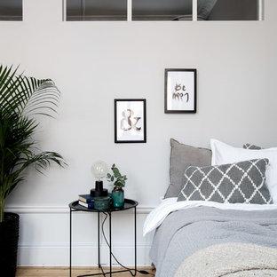 Ejemplo de habitación de invitados escandinava, de tamaño medio, con paredes grises y suelo de madera clara