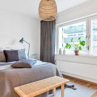 Idéer för skandinaviska gästrum, med vita väggar, mellanmörkt trägolv och beiget golv