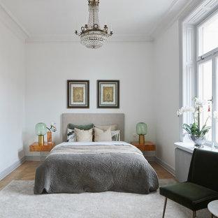 Foto på ett nordiskt sovrum, med vita väggar, ljust trägolv och beiget golv